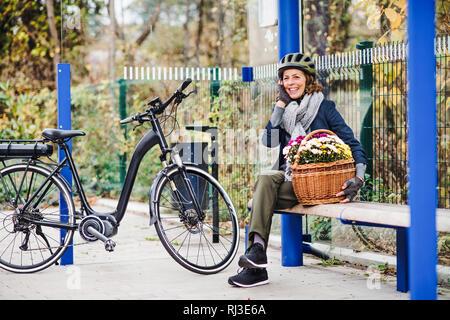 A senior woman avec electrobike et fleurs assise sur un banc à l'extérieur de la ville. Banque D'Images