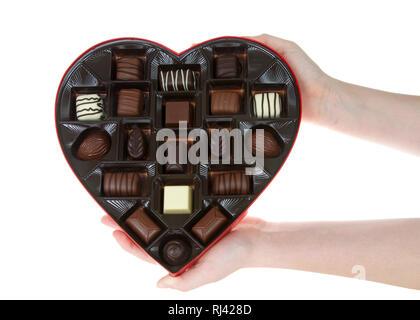 Hands holding Heart shaped box avec confiserie Chocolat isolé sur fond blanc. Un cadeau populaire pour la Saint Valentin. Banque D'Images
