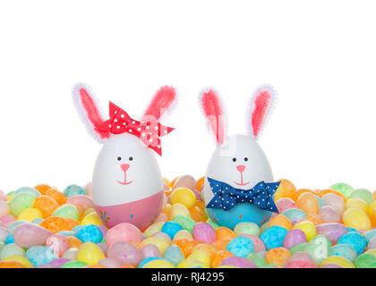 Conçu dans des oeufs de pâques lapins, garçon et fille, portant cravate d'arc et l'arc sur l'aer assis dans un tas de bonbons haricots tachetés. Banque D'Images