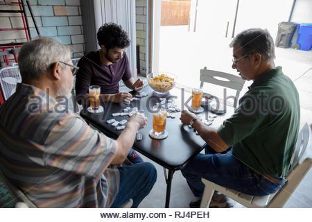 Latinx Men playing dominos en garage Banque D'Images