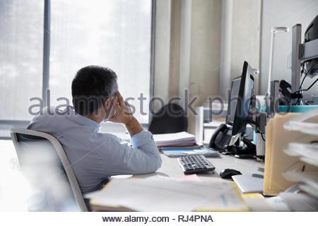 Thoughtful businessman at office desk Banque D'Images