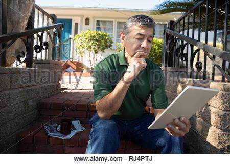 Latinx senior man using digital tablet sur avant stoop Banque D'Images