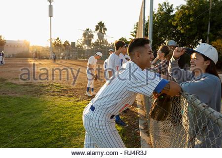 Joueur de baseball heureux de parler de petite amie à fence Banque D'Images