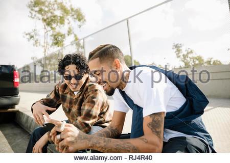 Les jeunes hommes Latinx amis à l'aide de smart phone sur trottoir urbain Banque D'Images