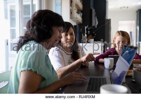 Fille Latinx senior enseignement mère comment utiliser l'ordinateur portable à la table de cuisine Banque D'Images