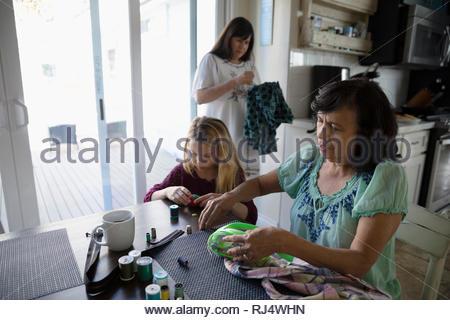 Latinx multi-generation couseuses à table de cuisine Banque D'Images