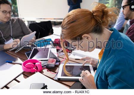 Millennial businesswoman using digital tablet at cafe Banque D'Images