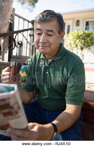 Latinx senior man reading newspaper et boire du café sur avant stoop Banque D'Images