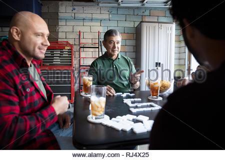 Les hommes sillonnent Latinx dominos en garage Banque D'Images