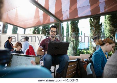 Au cours de l'ordinateur portable à l'aide de hackers mâle hackathon sur patio Banque D'Images