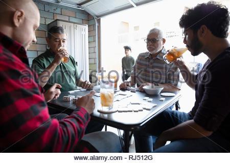 Latinx Hommes buvant du thé glacé et jouer aux dominos dans garage Banque D'Images