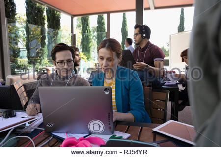 Businessman and businesswoman using laptop on patio Banque D'Images