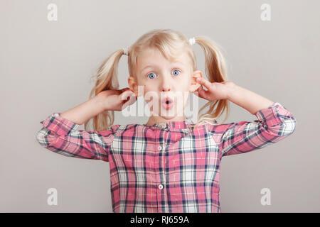 Closeup portrait of young blonde drôle preschool girl making faces en face de la caméra. Enfant tenant en tirant les oreilles faisant glisser sur un fond clair. Ki Banque D'Images