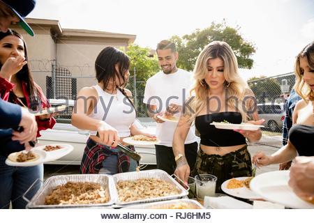 Latinx friends enjoying tacos au stationnement Banque D'Images