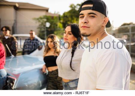 Portrait jeune homme Latinx confiant avec vos amis dans le parc de stationnement Banque D'Images