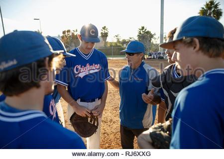 Coach et joueurs de baseball en caucus sur terrain ensoleillé Banque D'Images