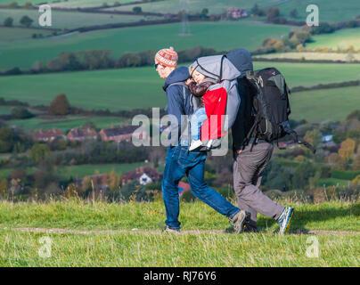 Couple de personnes marchant dans la campagne portant un enfant dans un porte-bébé sac à dos porter des chapeaux et manteaux un jour froid de l'automne, West Sussex, UK