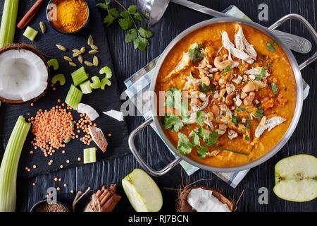 Vue de dessus de la soupe Mulligatawny copieux dans un chaudron sur une table en bois noir avec une louche et les ingrédients, des plats traditionnels indiens et anglais cu Banque D'Images