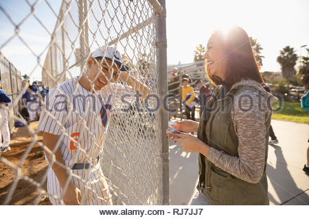 Joueur de baseball Latinx heureux de parler de petite amie à clôture ensoleillée Banque D'Images