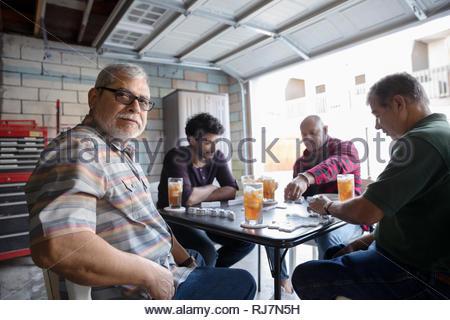 Portrait Latinx hommes jouant aux dominos dans garage Banque D'Images