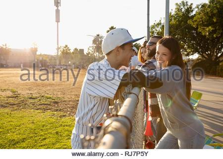 Joueur de baseball à parler de petite amie à clôture ensoleillée Banque D'Images