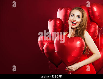 Happy woman in red dress holding balloons cœur rouge sur fond rouge. Cheerful surpris girl with red lips makeup et sourire mignon. Surprise, v Banque D'Images