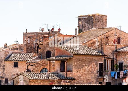 San Gimignano, Italie sur le toit avec la vieille ville historique de bâtiments médiévaux de la ville d'orange en été village en pierre tuiles libre et paraboles capitales