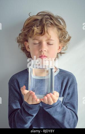 Sweet little boy en gardant les yeux fermés et holding glass Vase avec de l'eau transparente tout en se tenant près de mur blanc Banque D'Images