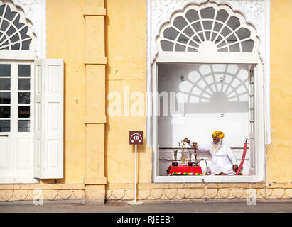 JODHPUR, Rajasthan, INDIA - Mars 08, 2015: Le Rajasthan vieil homme à barbe blanche près de la chicha et autres symboles traditionnels de la vie royale Mehrangarh en f Banque D'Images