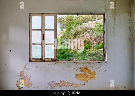 Intérieur d'une maison en ruine avec vieux, sale et fissuré mur blanc et d'une vitre cassée sur châssis à la prairie view