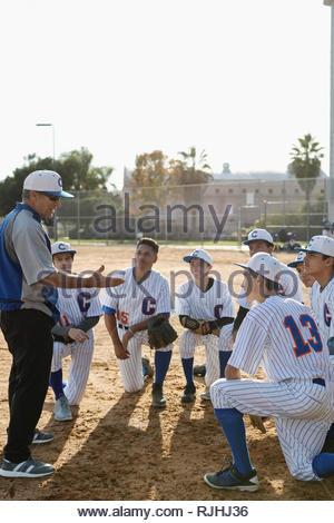 Coach et joueurs de baseball en caucus sur terrain Banque D'Images