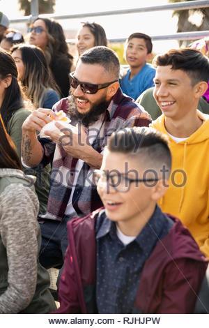 Heureux Latinx fans dans les gradins de manger et regarder un match de baseball Banque D'Images