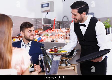 Poli jeune serveur ce qui porte l'ordre des plats de fruits de mer au restaurant de poissons à couple smiling Banque D'Images