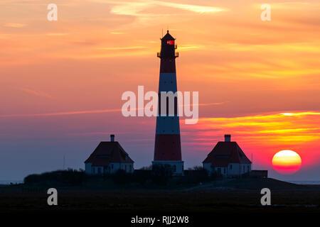Le phare Westerheversand au coucher du soleil. Presqu'île d'Eiderstedt, Frise du Nord, Allemagne Banque D'Images