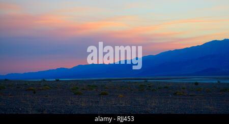Rose teinté par le soleil couchant, la fumée d'un feu lointain dérive sur les montagnes et dans la vallée de la mort. Banque D'Images