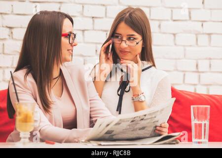 Deux jeunes femmes sont le démarrage d'une entreprise ensemble, à un bureau d'affaires à vendre dans le journal Banque D'Images