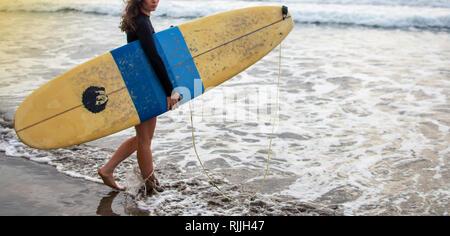 Young attractive et heureux surfer girl dans belle plage de surf jaune autour de l'océan profiter de vacances d'été à l'île tropicale Banque D'Images