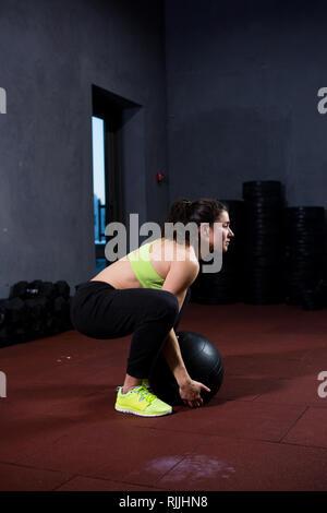 Thème le sport et la santé. Une forte femme caucasienne musculaire dans la salle de remise en forme de force et d'endurance. L'équipement d'un grand ballon noir imprimé soulève et Banque D'Images