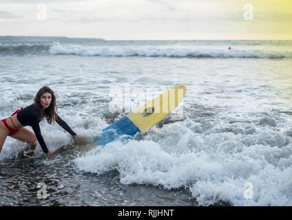 Jeune fille en bikini - surfer avec planche de surf sous l'eau plongée avec plaisir sous les grandes vagues de l'océan. L'eau de vie de famille, les gens et les leçons du sport beach Banque D'Images