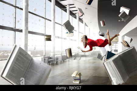 Relaxed woman fait léviter dans la salle pleine de voler des livres. Technique mixte Banque D'Images
