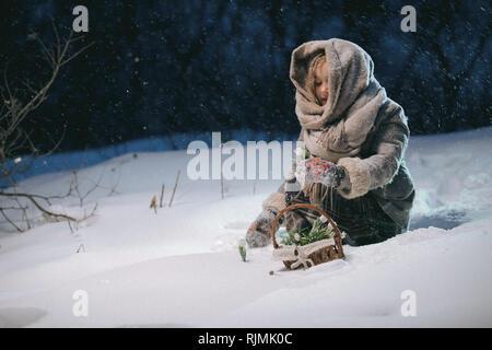 Jolie petite fille enfant perçoit en premier panier de fleurs sous la neige en hiver. soir nuit fantastique. châssis comme illustration pour le conte de fées 12 mois Banque D'Images
