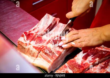 Coupe femme boucher morceau de viande de côtes dans sa boutique avec un couteau. Banque D'Images