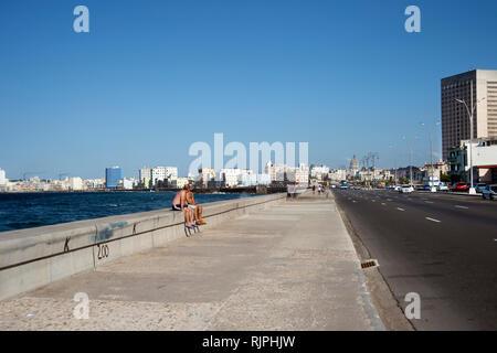 Deux hommes cubains torse nu assis sur le mur de la mer le Malecon face au large boulevard Malecon de La Havane Cuba Banque D'Images