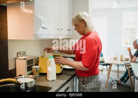 Femme mature est de mettre les tranches de pain blanc dans un grille-pain à la maison pour son petit-déjeuner. Banque D'Images