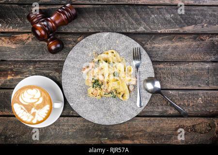 Les pâtes italiennes Les pâtes dans une sauce crémeuse aux crevettes sur une assiette, servi avec les couverts et de tasse de café, décoré de deux moulins à poivre. Banque D'Images