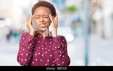 Beau young african american woman wearing head scarf sur fond isolé avec la main sur la tête pour la douleur dans la tête parce que le stress. Souffrance migrai Banque D'Images