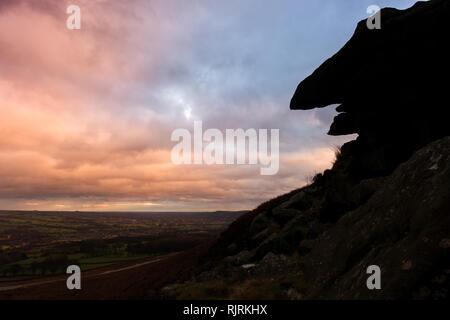 Coucher de soleil sur la pierre à crêpes qui, lorsque la silhouette, ressemble à un visage, Ilkley Moor et Burley Moor à l'ensemble Wharfedale Banque D'Images