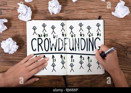 Une vue de dessus d'une Businesswoman's hand drawing Concept Crowdfunding texturé en bois sur 24