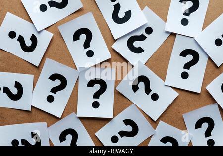 Interrogation sur les cartes papier répartis au hasard sur un fond de bois dans une image conceptuelle Banque D'Images