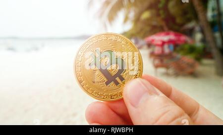Main tenant bitcoin d'or sur la plage, sur le fond de mer vague. Bitcoin est une façon moderne d'échange cette crypto-monnaie est un moyen très pratique